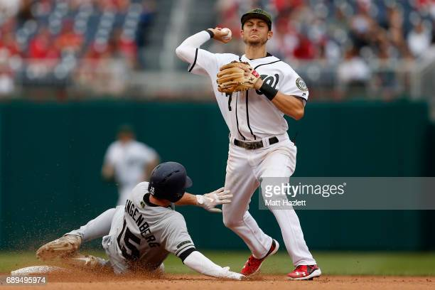 Trea Turner of the Washington Nationals attempts to turn a double play over Cory Spangenberg of the San Diego Padres for the second out of the eighth...