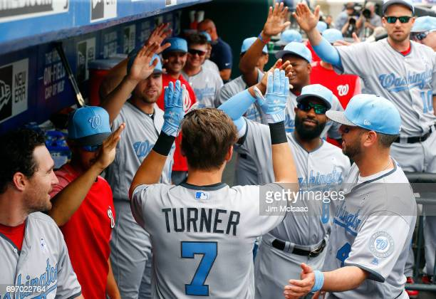 Trea Turner of the Washington Nationals celebrates his first inning home run against the New York Mets with his teammates in the dugout at Citi Field...