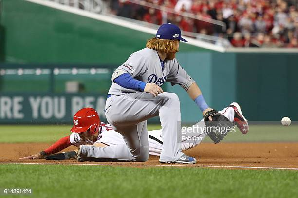 Trea Turner of the Washington Nationals dives into third base against Justin Turner of the Los Angeles Dodgers in the third inning during game five...