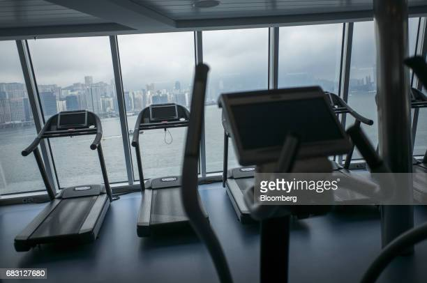 Treadmills stand at a windowm inside a gym room on board the Ovation of the Seas Quantumclass cruise ship operated by Royal Caribbean Cruises Ltd at...
