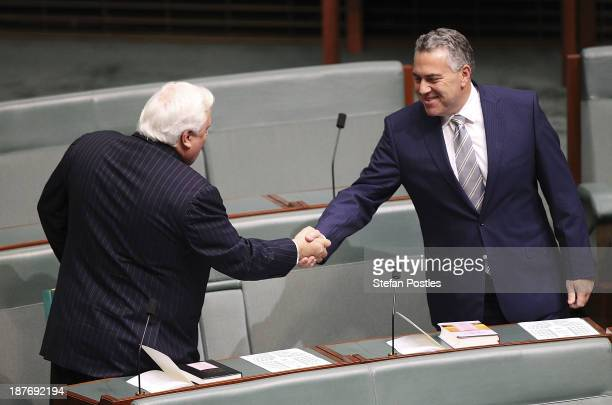 Treasurer Joe Hockey shakes hands with Clive Palmer prior to a swearing in ceremony in the House of Representatives chamber at Parliament House on...