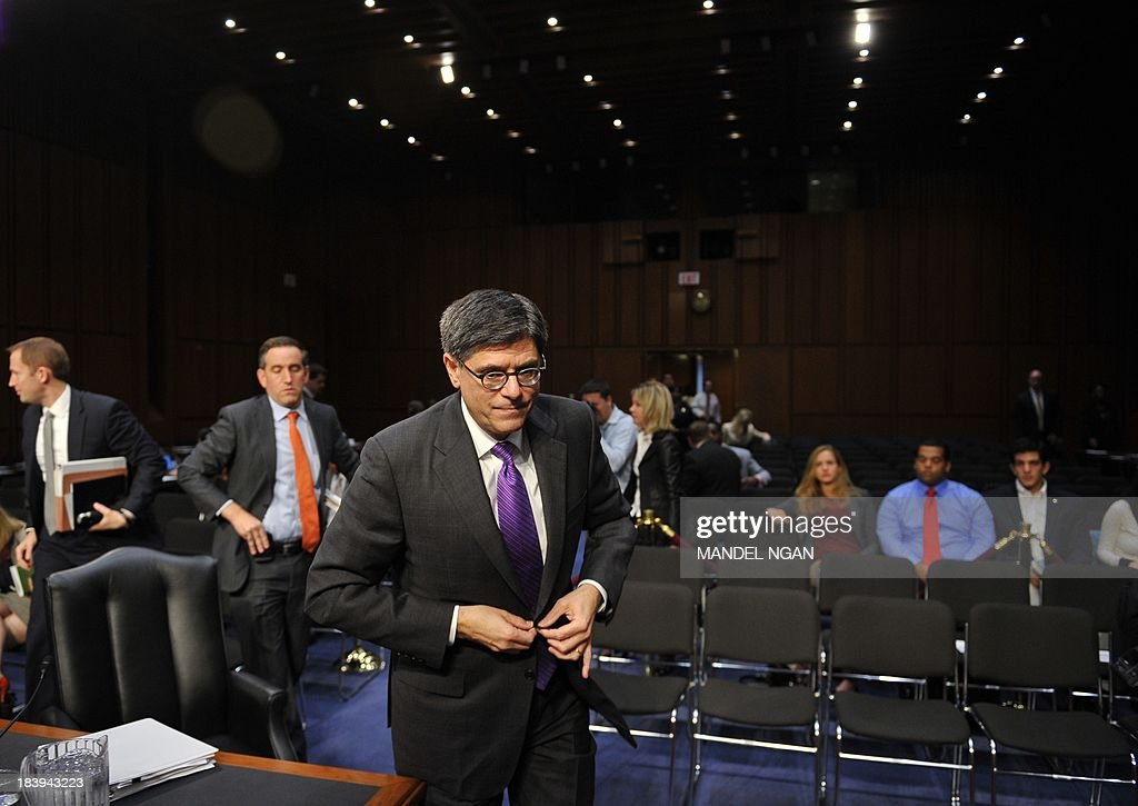 US Treasury Secretary Jacob Lew buttons his jacket after testifying to Senate Finance Committee on the debt limit in the Hart Senate Office Building on Capitol Hill in Washington, DC on October 10, 2013. AFP PHOTO/Mandel NGAN