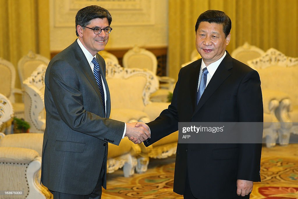 US Treasury Secretary Jacob Lew, (L) shakes hands with Chinese President Xi Jinping during their meeting at the Great Hall of the People in Beijing on March 19, 2013. Lew's visit to China comes with tensions between the countries having risen recently amid US allegations that China has engaged in hacking against US companies, which Washington warned could damage relations. AFP PHOTO / POOL / FENG LI