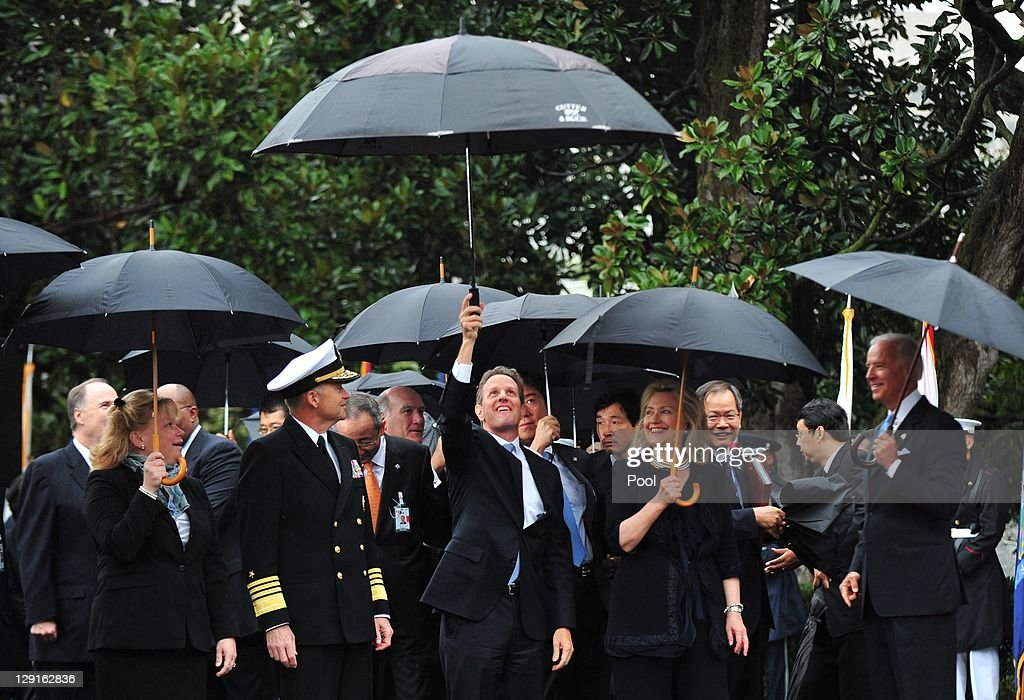 U.S. Treasury Secretary Tim Geithner holds up his umbrella during an arrival ceremony for South Korean President Lee Myung-bak on the South Lawn of the White House October 13, 2011 in Washington, D.C. Later in the day Lee is scheduled to hold a joint press conference with Obama and also address a joint meeting of Congress.