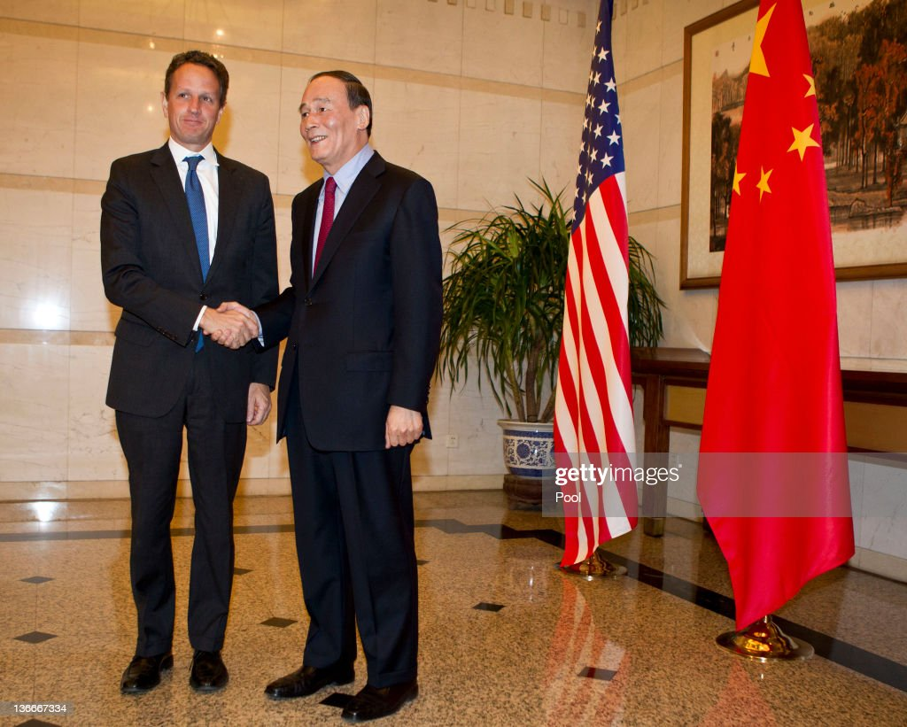 Treasury Secretary Timothy Geithner shakes hands with Chinese Vice Premier Wang Qishan before attending a dinner at the Diaoyutai State Guesthouse on...