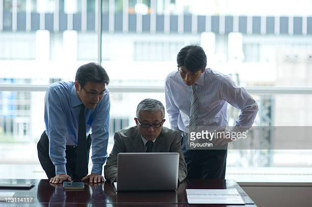 tree businessmen who are looking at personal compu