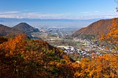 Tree covered mountain range and small town in autumn. Yamagata Prefecture, Japan