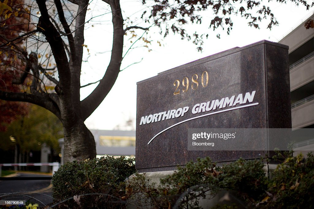 A tree stands next to a Northrop Grumman Corp. sign outside the company's headquarters in Falls Church, Virginia, U.S., on Friday, Nov. 16, 2012. President Barack Obama expressed confidence that he and Congress would reach an agreement that will avoid the automatic spending cuts and tax increases that are scheduled to occur at the end of the year. The fiscal cliff is the $607 billion combination of automatic spending cuts and tax increases scheduled to take effect in January. Lawmakers are trying to avert the cliff to prevent a short-term shock to the economy and reach an agreement on long-term deficit reduction. Photographer: Andrew Harrer/Bloomberg via Getty Images