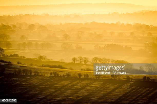 Trees cast long shadows through the mist and fog as it hangs in valleys on the Mendip hills Somerset at sunrise after a night of freezing fog and...