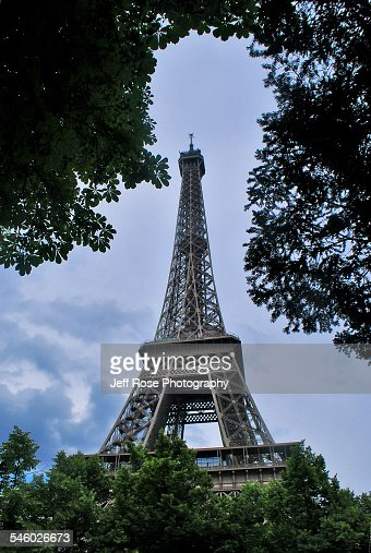 trees frame the eiffel tower in paris france stock photo