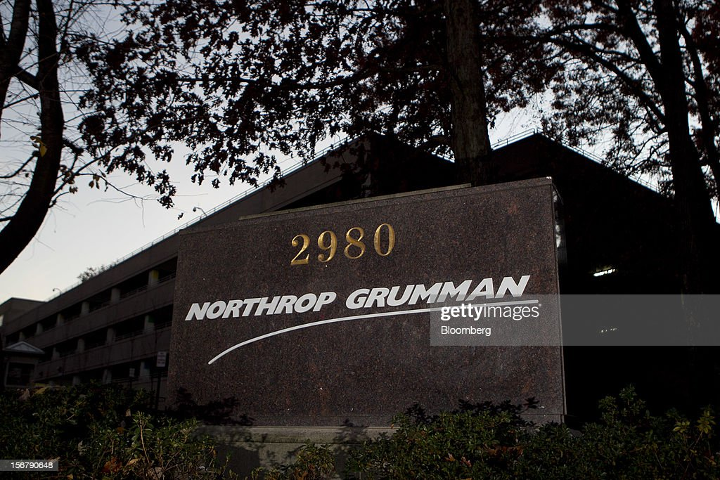 Trees stand next to a Northrop Grumman Corp. sign outside the company's headquarters in Falls Church, Virginia, U.S., on Friday, Nov. 16, 2012. President Barack Obama expressed confidence that he and Congress would reach an agreement that will avoid the automatic spending cuts and tax increases that are scheduled to occur at the end of the year. The fiscal cliff is the $607 billion combination of automatic spending cuts and tax increases scheduled to take effect in January. Lawmakers are trying to avert the cliff to prevent a short-term shock to the economy and reach an agreement on long-term deficit reduction. Photographer: Andrew Harrer/Bloomberg via Getty Images