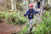 Boy in a harness on a treetop adventure park walking across a rope bridge