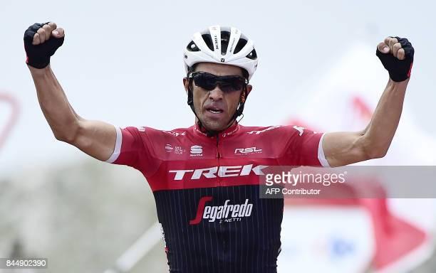 Trek Segafredo's Spanish cyclist Alberto Contador celebrates as he crosses the finish line winning the 20th stage of the 72nd edition of 'La Vuelta'...