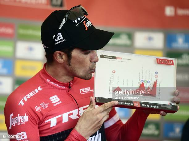 Trek Segafredo's Spanish cyclist Alberto Contador kisses a trophy as he celebrates on the podium winning the 20th stage of the 72nd edition of 'La...