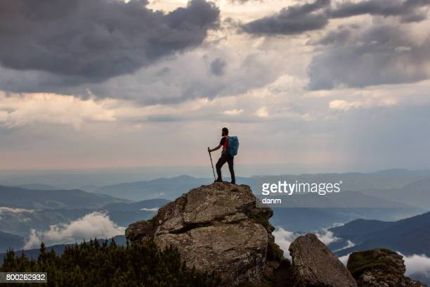 Trekker hiking on a mountain with beautiful storm clouds in background