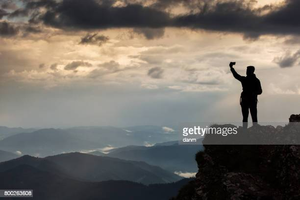 Trekker taking selfie on a mountain with beautiful storm clouds in background