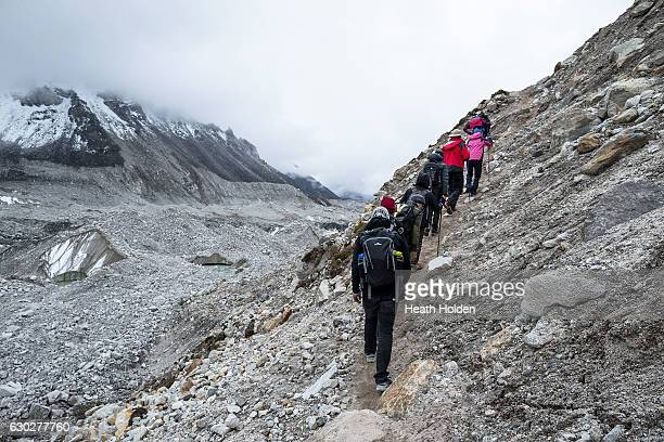 Trekkers making their way back to Gorak Shep after visiting Everest base camp The Khumbu glacier on the left is receding due to climate change pools...