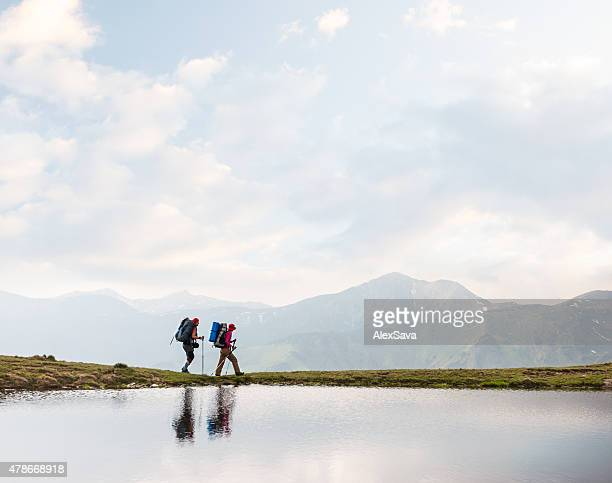 Trekkers walking along a clear lake in the mountains