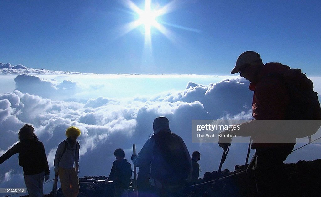 Trekkers watch the first sunrise from the summit of Mt. Fuji on July 1, 2014 in Fujiyoshida, Yamanashi, Japan. The climbing season is until September.