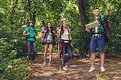 Trekking, camping and wild life concept. Four best friends are hiking in the spring woods, the guy is showing the direction, lady is checking it on a map, all are excited and anxious