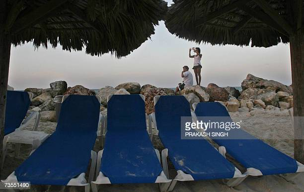 This picture taken on 09 March 2007 shows a tourist couple enjoy the sunset on beach of Starfish resort in Trelawney Jamaica Jamaica is the third...