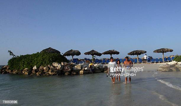 This picture taken on 09 March 2007 shows tourists as they walk on a beach at Starfish resort in Trelawney Jamaica is the third largest island in the...