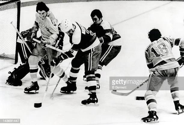 C Tremblay and Francois Lacombe of the Quebec Nordiques try to control the puck in front of goalie Richard Brodeur as Denis Miloche and John...