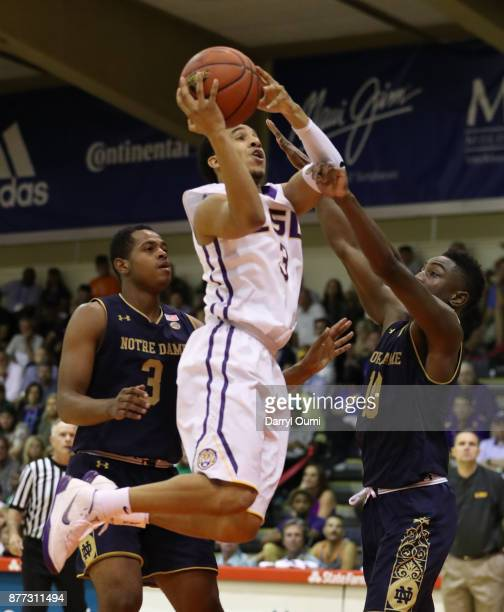 Tremont Waters of the LSU Tigers tries to aviod Temple 'TJ' Gibbs Jr #10 of the Notre Dame Fighting Irish as he shoots during the second half of...