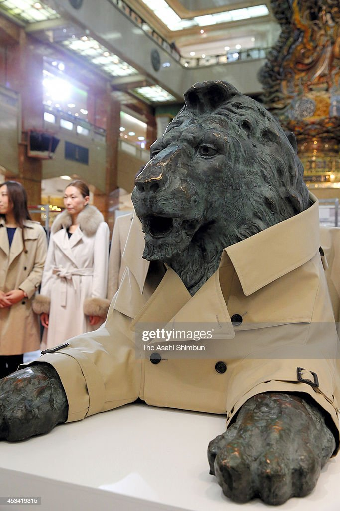 Trench coat wearing lion statues are on display at Mitsukoshi Department Store Nihombashi Branch on December 4, 2013 in Tokyo, Japan. The lion statues are the symbol of the department store chain and the trench coat were tailored by apparel maker Sanyo Shokaito celebrate a century anniversary of the statues.
