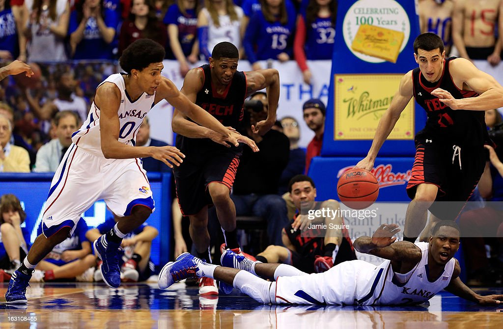 Trency Jackson #1 of the Texas Tech Red Raiders scrambles against Kevin Young #40 and Jamari Traylor #31 of the Kansas Jayhawks for a loose ball during the game at Allen Fieldhouse on March 4, 2013 in Lawrence, Kansas.