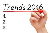 Hand writing Trends for 2016 list with marker on transparent wipe board isolated on white.