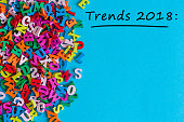 Trends 2018 - text at blue background with many little letters and empty space for text, mock up. New trend, fashion, colors, innovations.