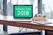 Trends for 2018 word in laptop computer screen with tablet on wood stood table in at window with blur background,Digital Business or marketing trending.