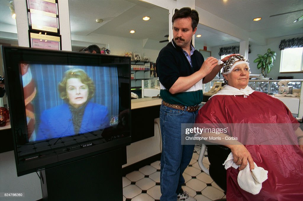 Trends Salon owner Steve Wesseler watches Dianne Feinstein on CNBC while working on a customer's perm