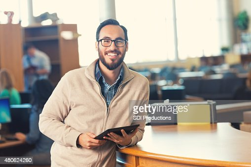 Trendy adult college student in library with digital tablet