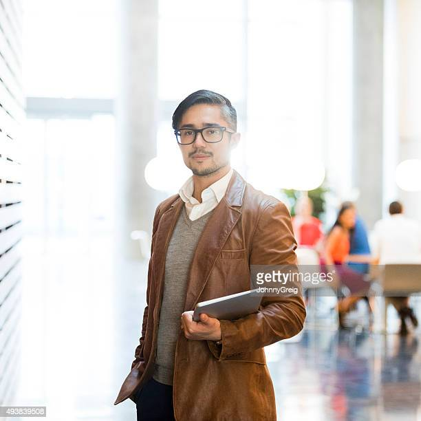 Trendy businessman wearing brown leather jacket holding laptop