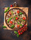 Trendy food Italian black pizza with tomatoes, basil and ham