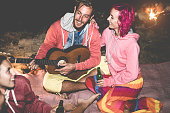 Trendy friends playing guitar and drinking beer next bonfire outdoor - Happy people having fun camping in vacation holidays - Focus on man face - Friendship, party and nature concept - Contrast filter