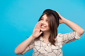 Young girl in shirt and hat holding hand on face telling secrets on blue background.
