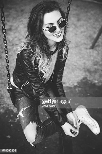 Trendy Girl Wearing Leather Jacket On Swingset