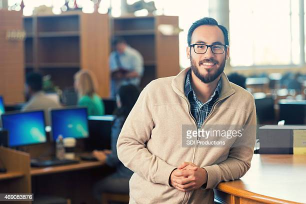Trendy Hispanic hipster man smiling in college library