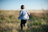 back of little boy running among the grass in blurred focus