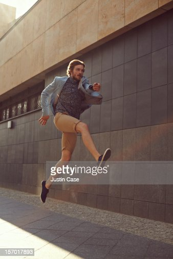 A trendy man jumping powerfull in the air : Stock Photo