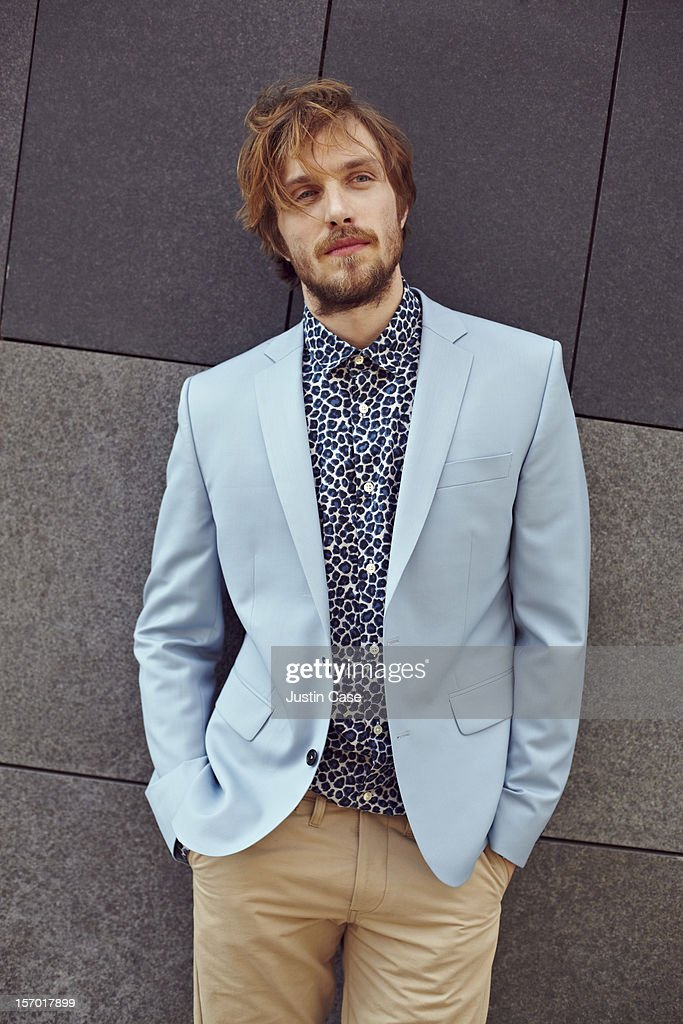 A trendy man leaning against a stone wall : Stock Photo
