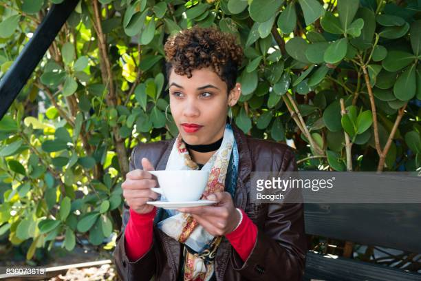 Trendy Millennial Mixed Race Woman Drinks Coffee  Outdoors Miami Florida