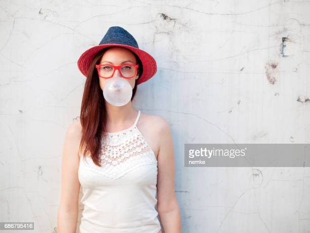 Trendy urban girl blows big bubble from bubble gum