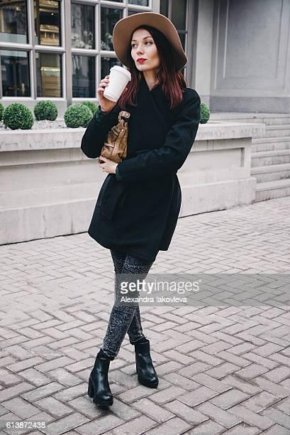 Trendy woman drinking take away coffee