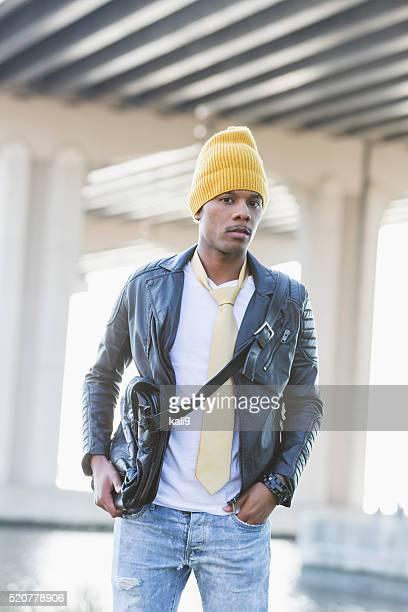 Trendige jungen schwarzen Mann im Freien trägt gelbe Mütze