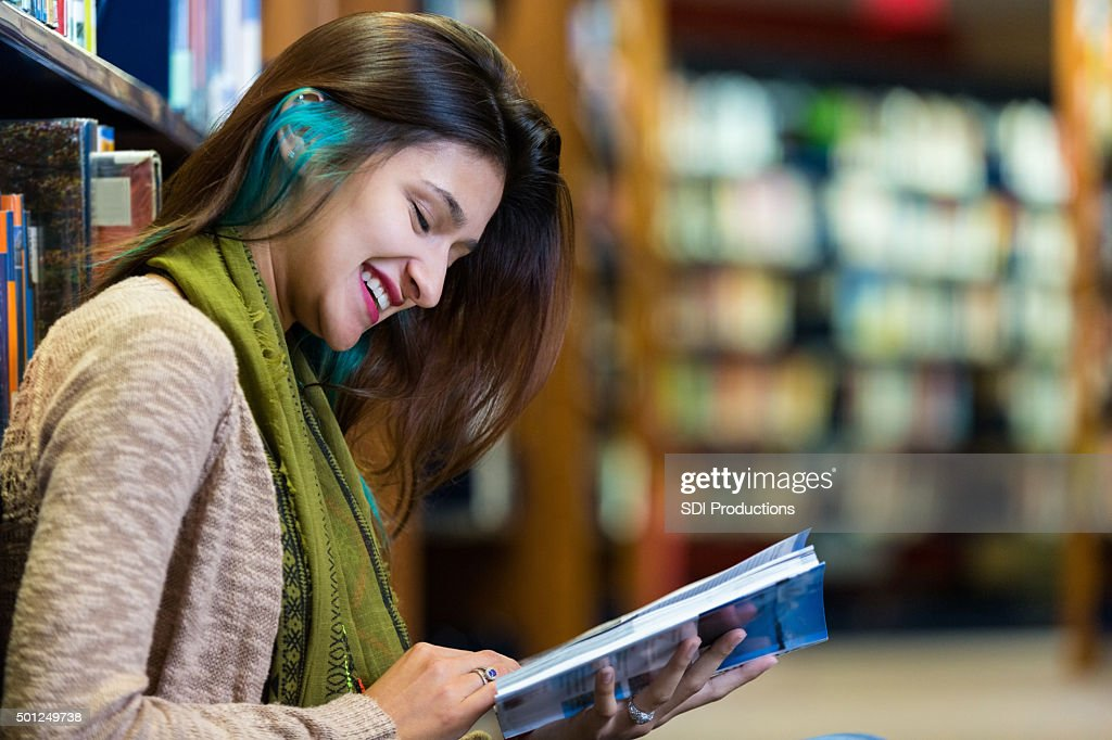 Trendy young college student reading in modern library : Stock Photo