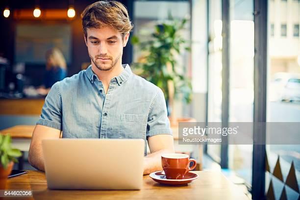 トレンディーな若い男性ノートパソコンを使うのカフェ